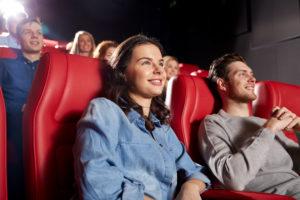 Ungdommer ser på film på kino og smiler