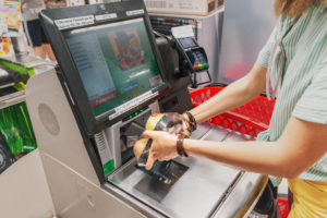 Hender som scanner inn varer på selvbetjent kasse