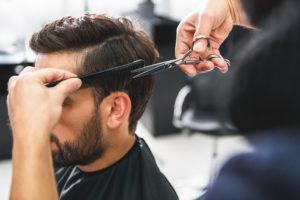 Mann som får håret sitt klippet hos frisør